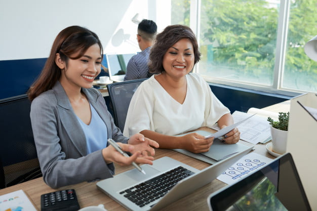 two asian female colleagues are sitting desk office with laptop one woman helping another 1098 17350