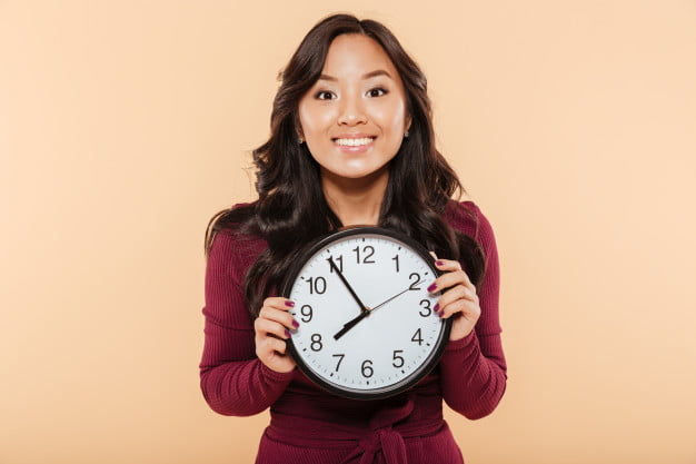 happy emotions asian woman with curly long hair holding clock showing nearly 8 waiting something pleasant peach background 171337 3578