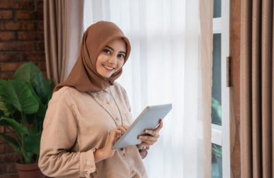 young beautiful woman veiled holding tablet looks camera standing near curtains windows 8595 10301 1