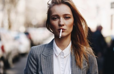 blonde girl with cigar stands street