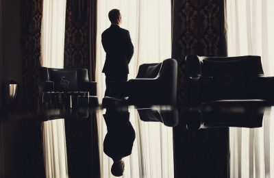 lonely man stands before window room