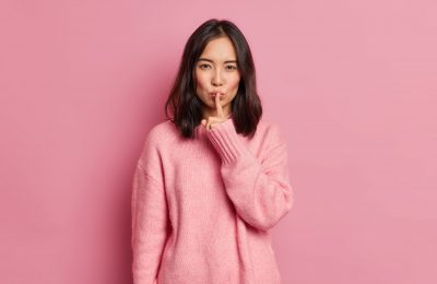 serious mysterious brunette asian woman presses index finger lips makes hush gesture tells secret asks be quiet wears long sleeved jumper poses